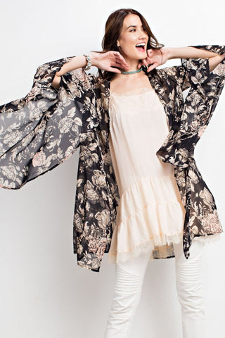 Front view woman wearing black/ivory floral print woven kimono cardigan with dramatic bell sleeves