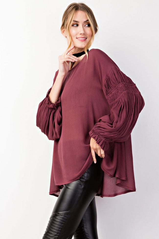 Side view young woman wearing plum ruched sleeve high low tunic top