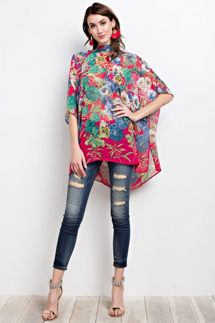 Full front view young woman wearing fuchsia floral print poncho-style tunic with tie back