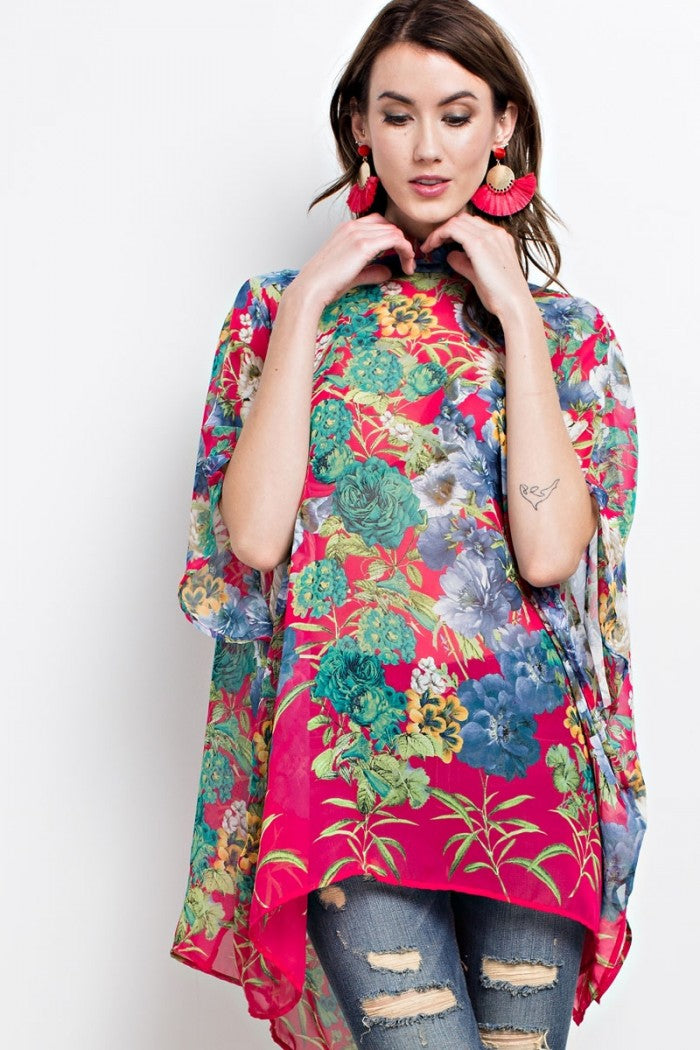 Front view young woman wearing fuchsia floral print poncho-style tunic with tie back
