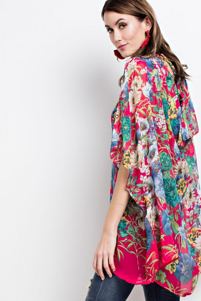 Back view young woman wearing fuchsia floral print poncho-style tunic with tie back