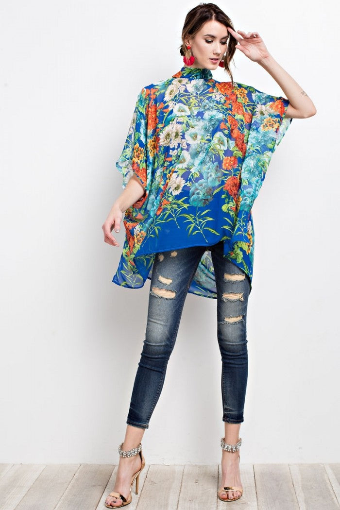 Full front view young woman wearing blue floral print poncho-style tunic with tie back