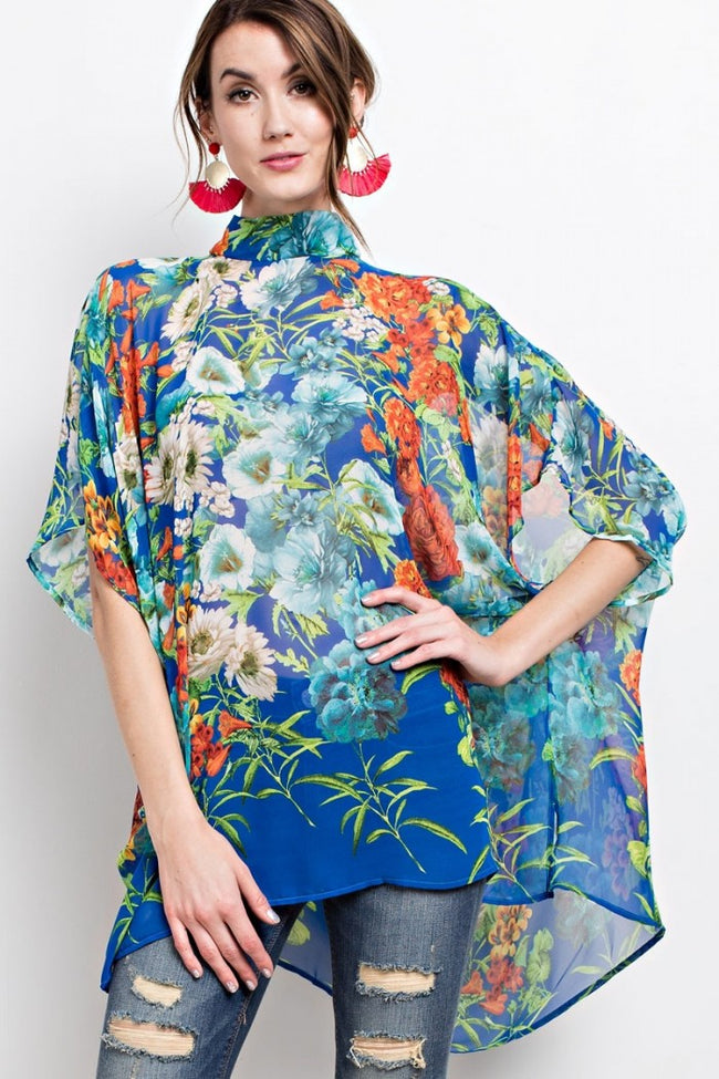 Front view young woman wearing blue floral print poncho-style tunic with tie back