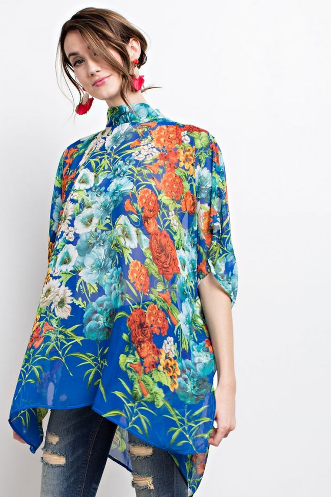 Front view young woman wearing blue floral print poncho-style tunic with tie back - 2