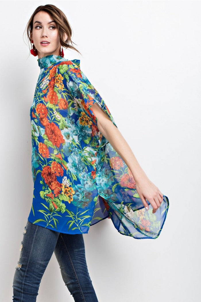Side view young woman wearing blue floral print poncho-style tunic with tie back