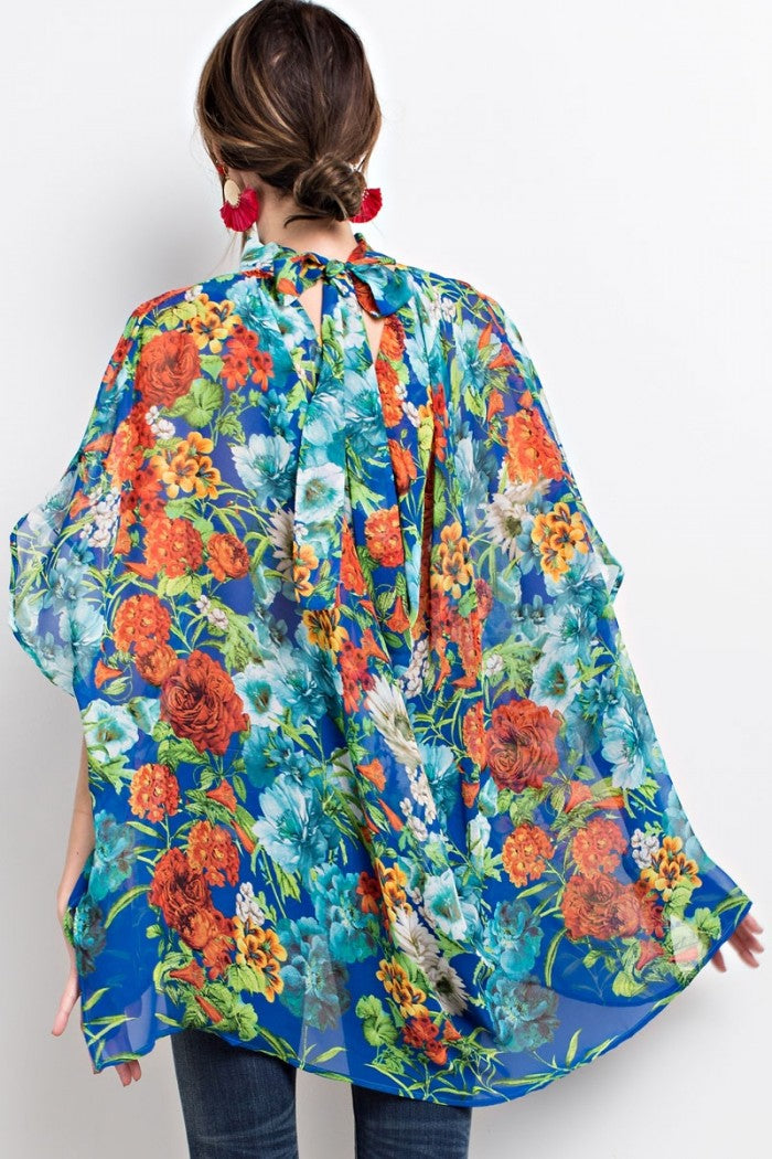 Back view young woman wearing blue floral print poncho-style tunic with tie back