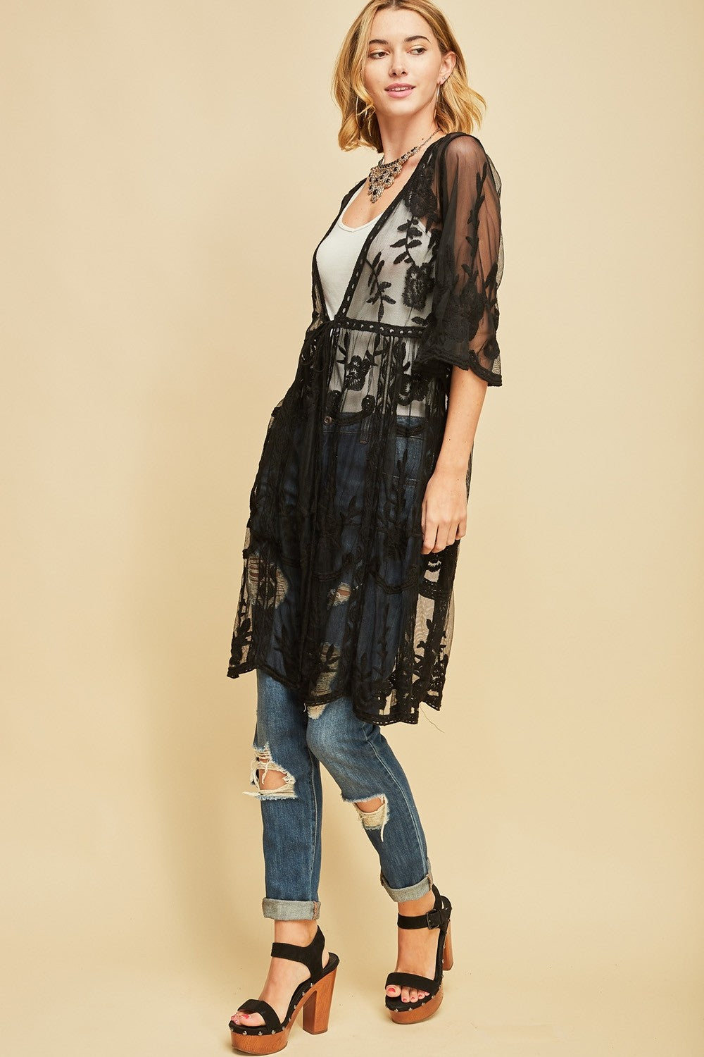 Left three quarter view woman wearing black empire waist tie front sheer floral embroidered kimono