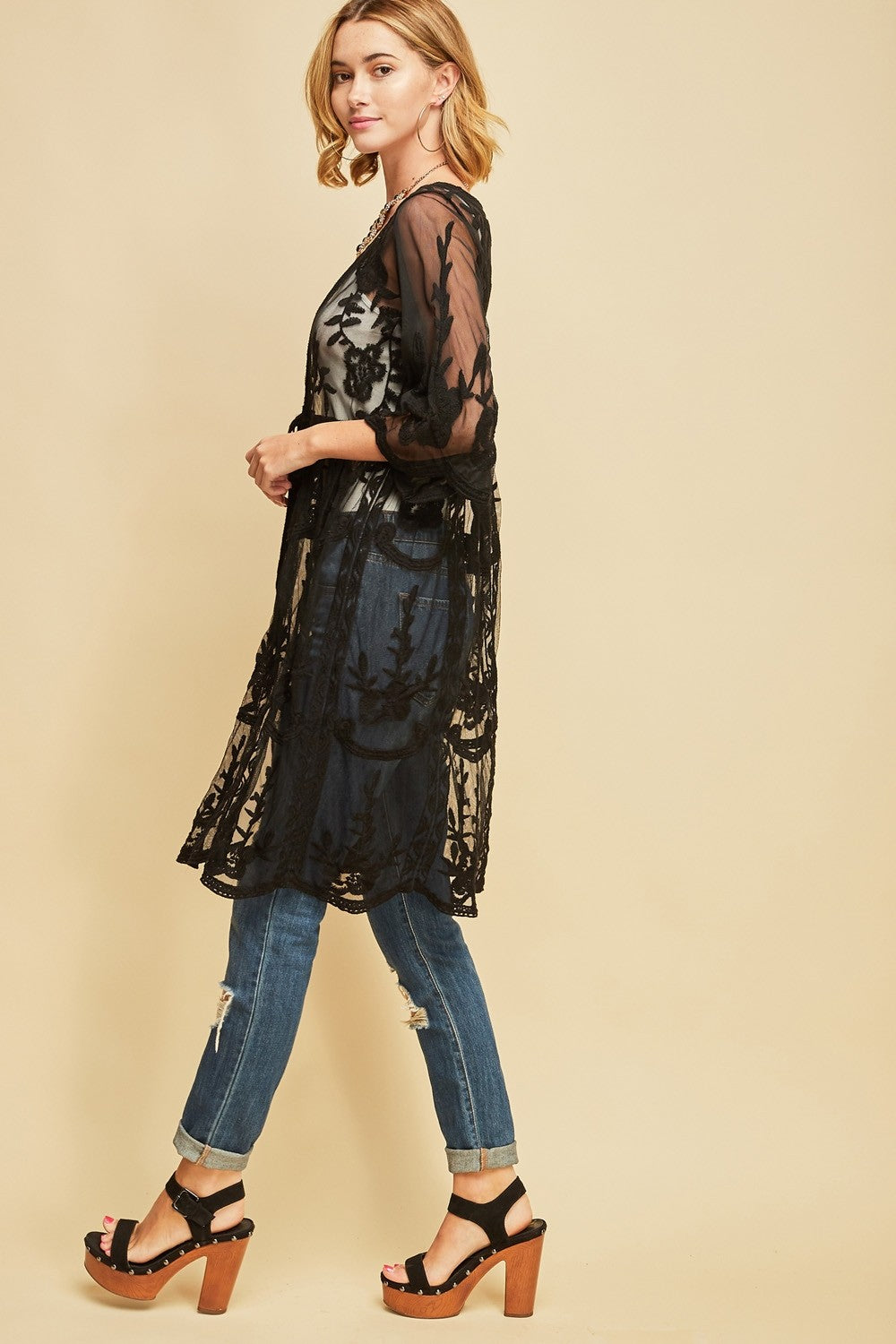 Left side view woman wearing black empire waist tie front sheer floral embroidered kimono
