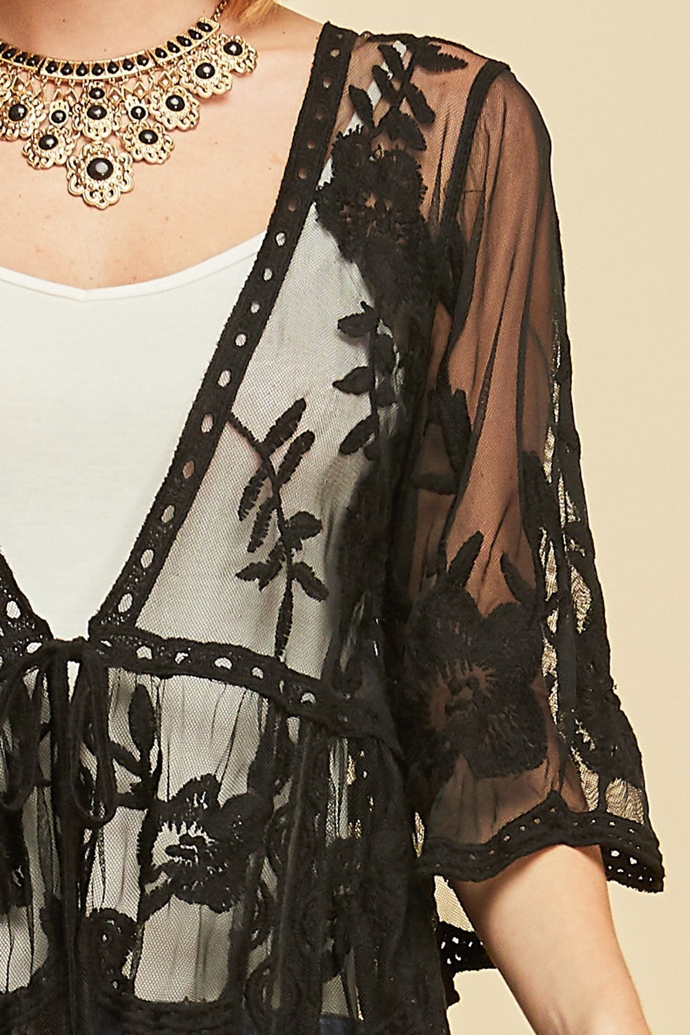 Front detail view woman wearing black empire waist tie front sheer floral embroidered kimono