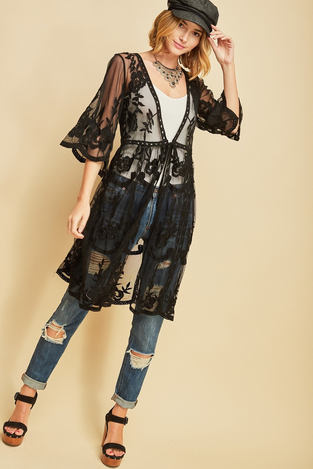 Front full view woman wearing black empire waist tie front sheer floral embroidered kimono and jeans