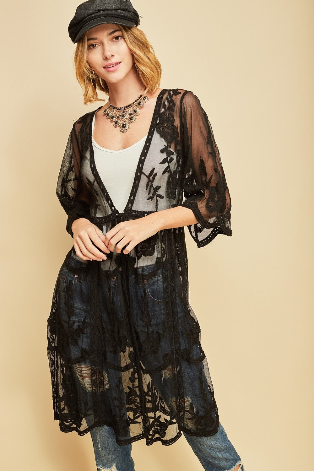 Front view young woman wearing black empire waist embroidered sheer cardigan