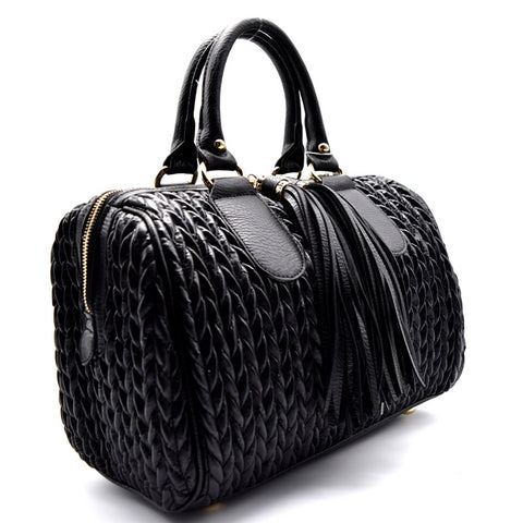 Right side view black quilted satchel handbag with two long tassel accents