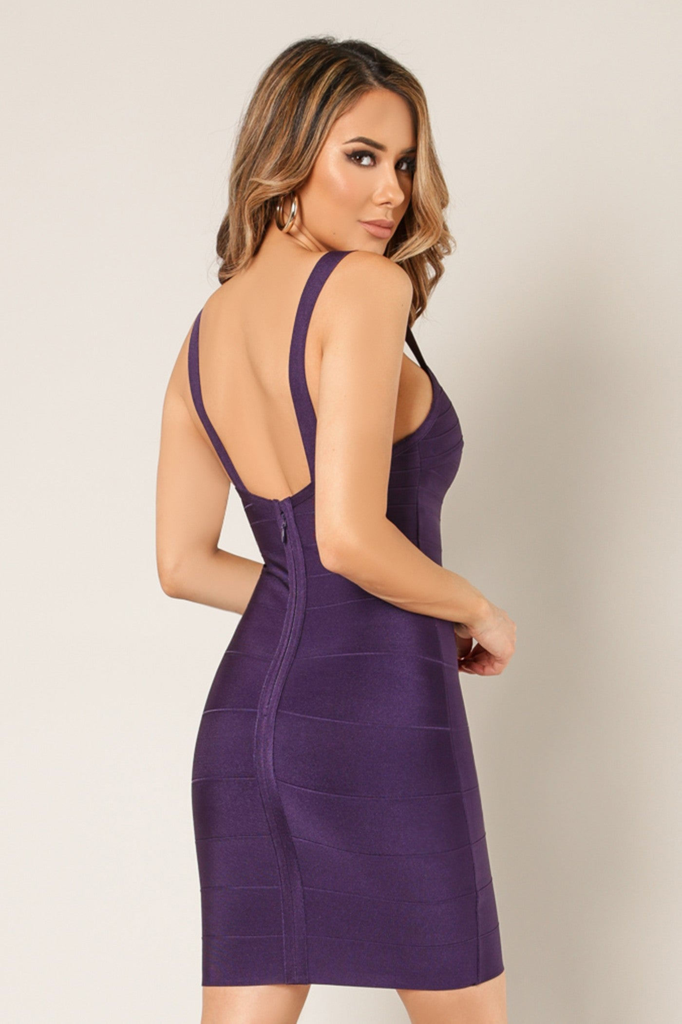 Back view young woman wearing eggplant bandage sexy club dress