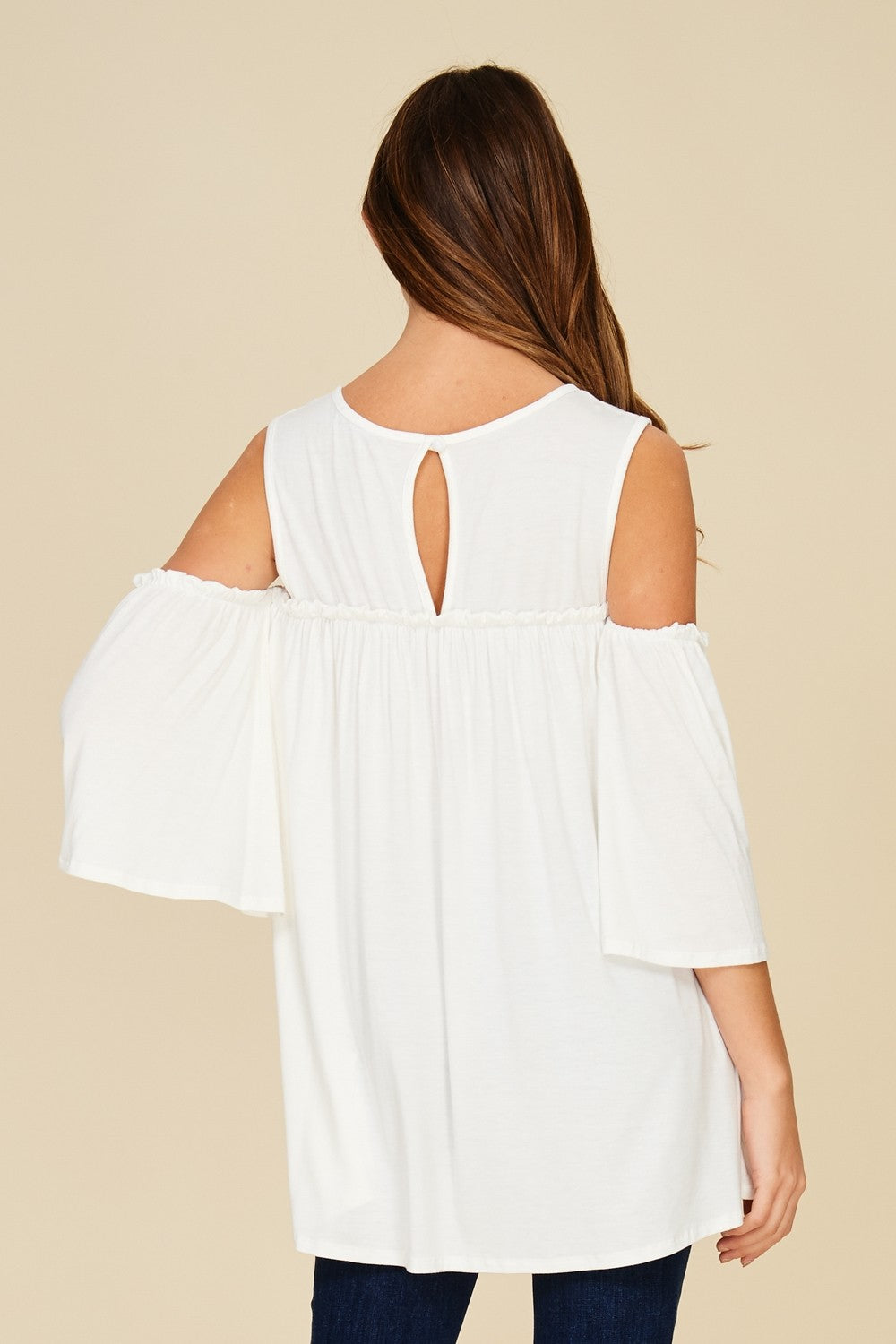 Back View White cold shoulder knit tunic top with three quarter bell sleeves