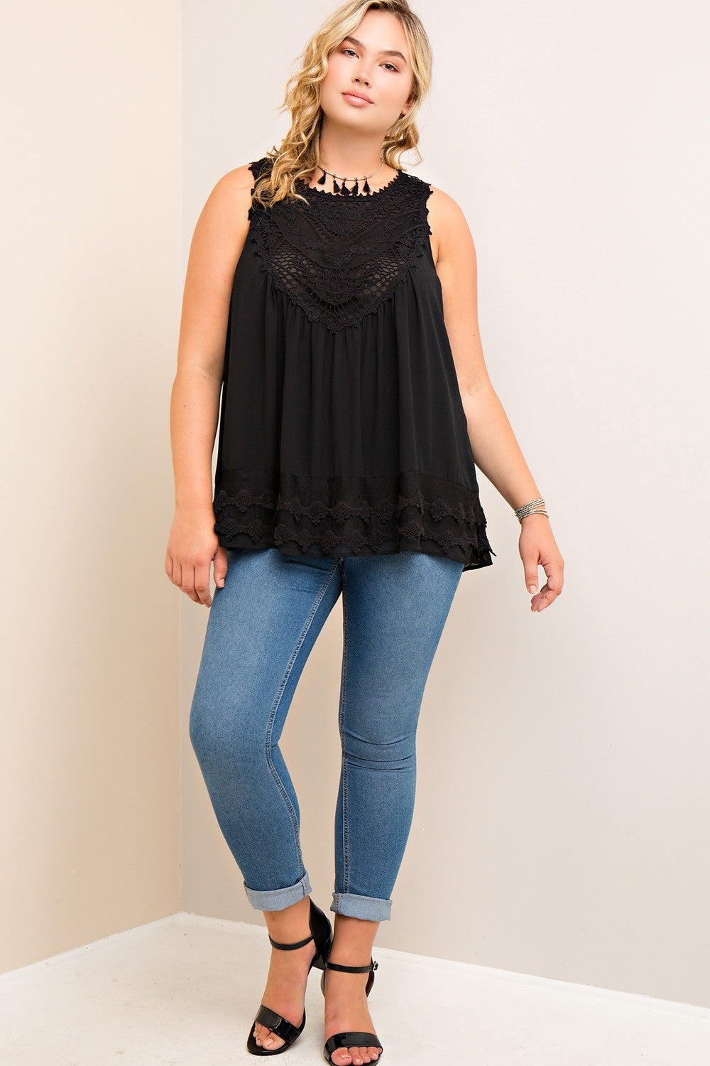 Full front view young plus size woman wearing black colored sleeveless crochet trim top