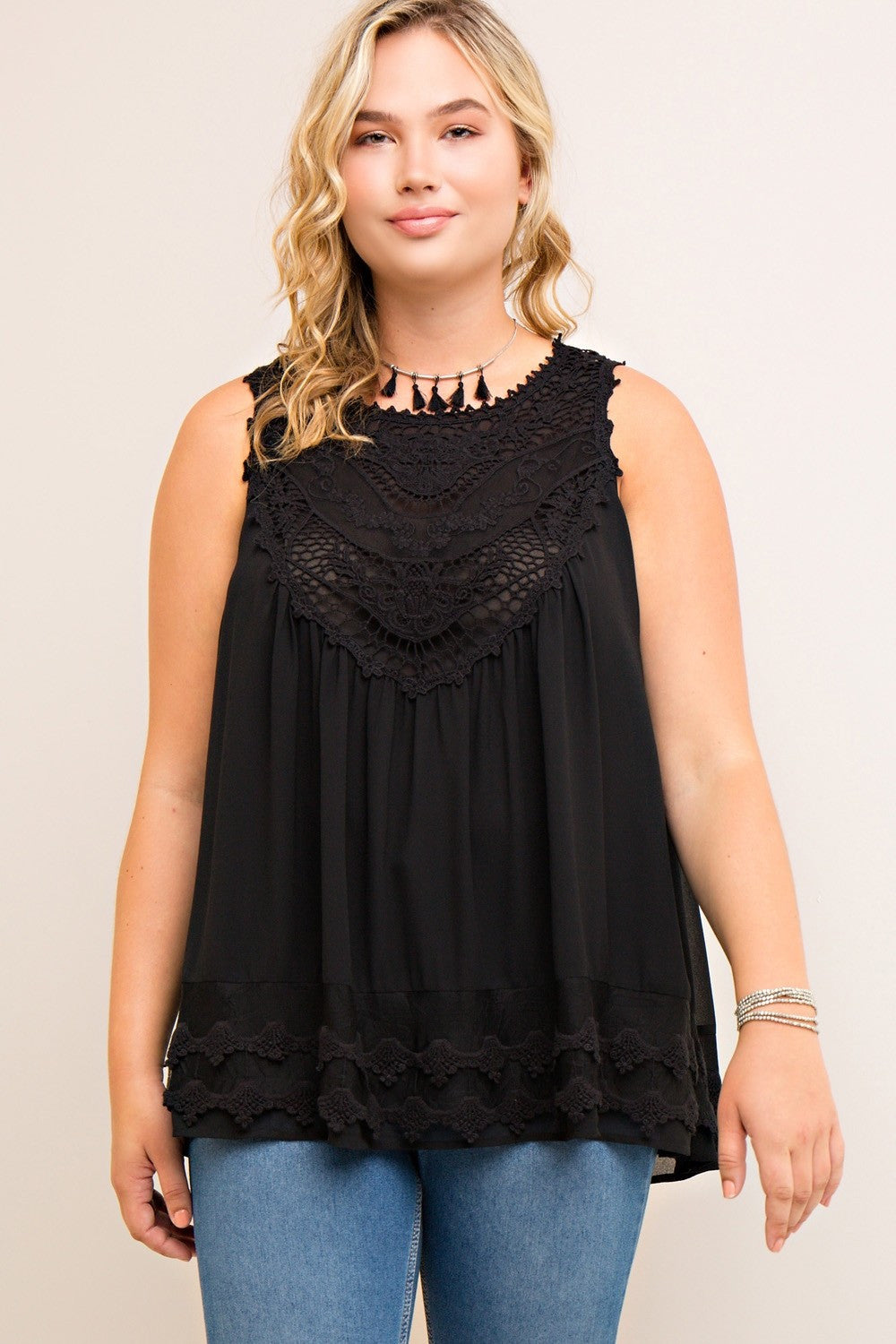 Front view young plus size woman wearing black colored sleeveless crochet trim top