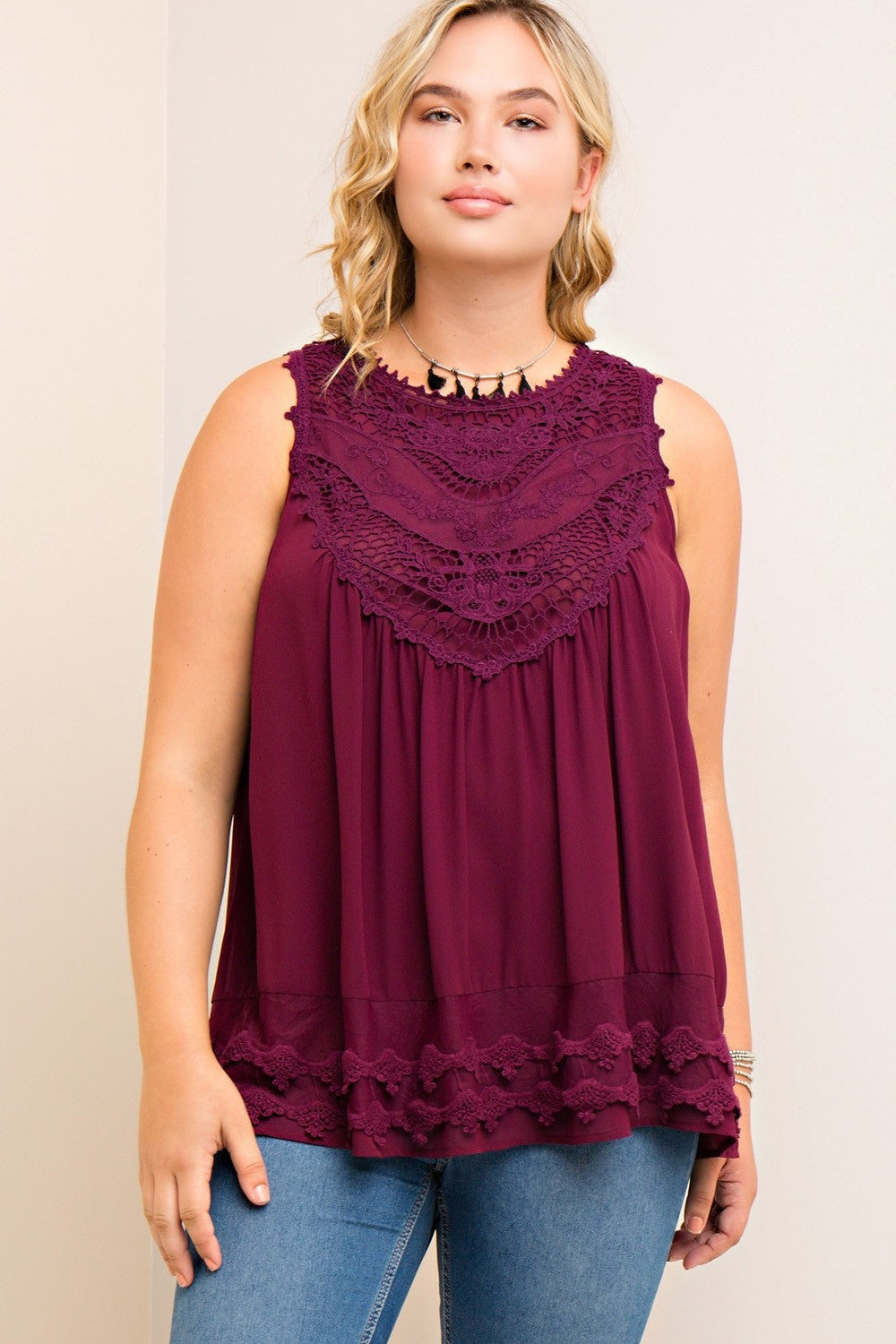 Front view young plus size woman wearing wine colored sleeveless crochet trim top