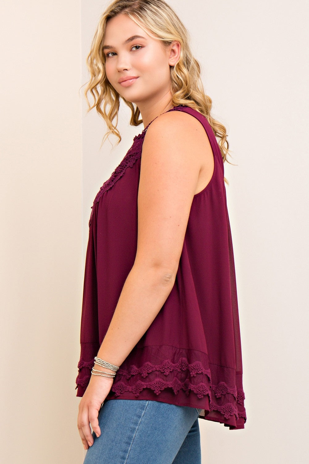 Side view young plus size woman wearing wine colored sleeveless crochet trim top