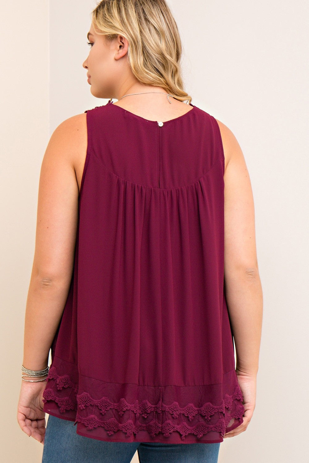 Back view young plus size woman wearing wine colored sleeveless crochet trim top