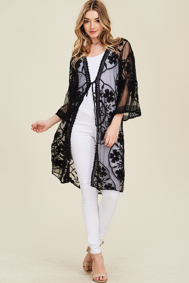 Front full view woman wearing black tie-front floral-embroidered mesh knee-length kimono cardigan