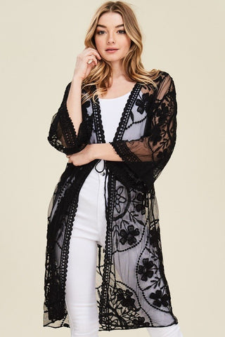 Front view young woman wearing black sheer mesh cardigan with floral embroidery