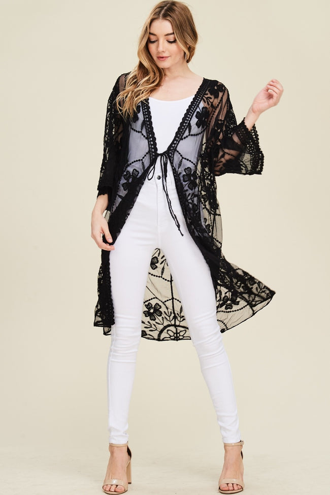 Full view woman wearing black tie-front floral-embroidered mesh knee-length kimono cardigan
