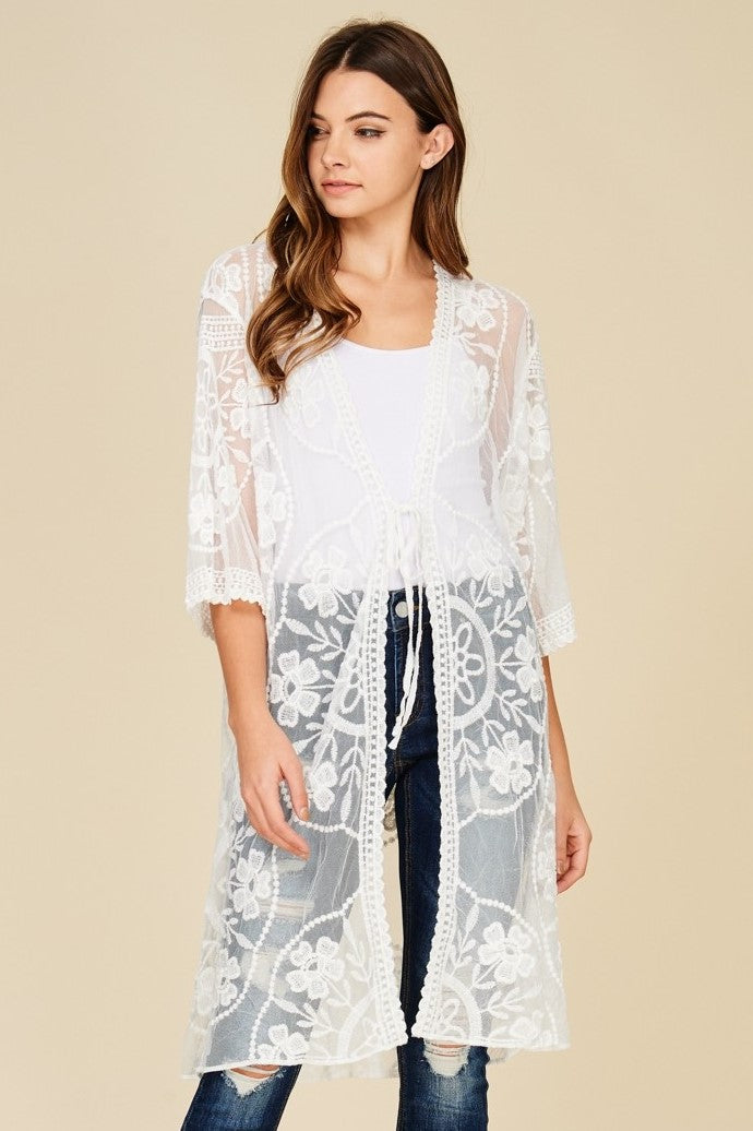 Front view young woman wearing white sheer mesh cardigan with floral embroidery