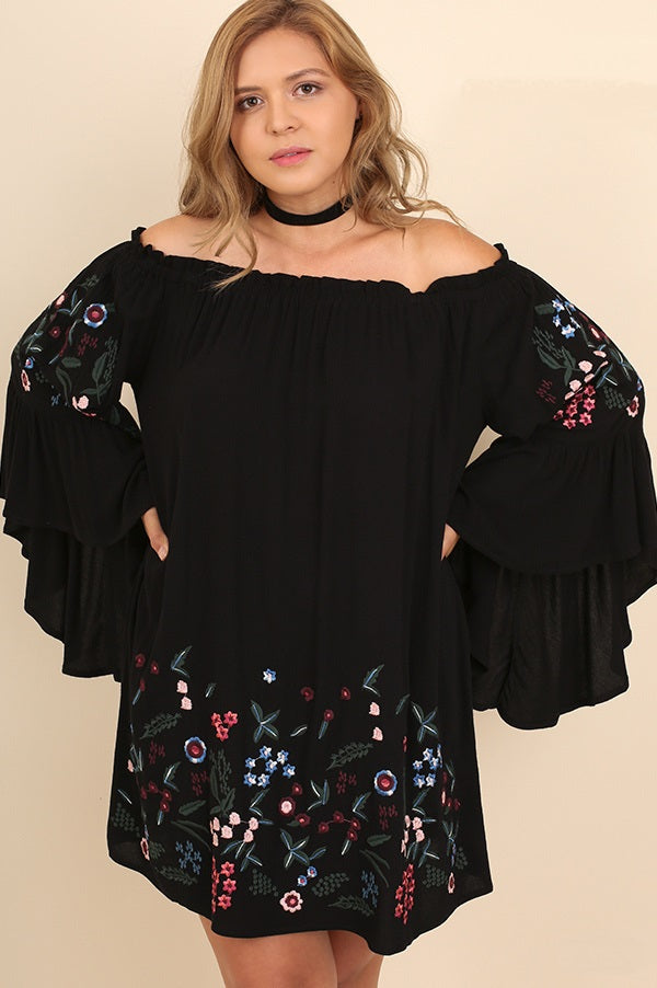 Front view plus size young woman wearing black floral-embroidered bell sleeve dress