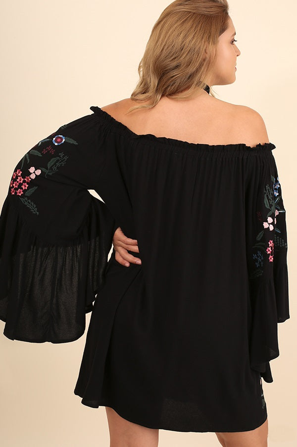 Back view plus size young woman wearing black floral-embroidered bell sleeve dress