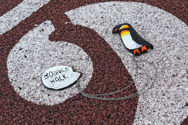 "Chain pin with cartoon inspired penguin ""I am Resilient"" II"