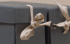 Grey upright museum archive box, with ribbon fasteners