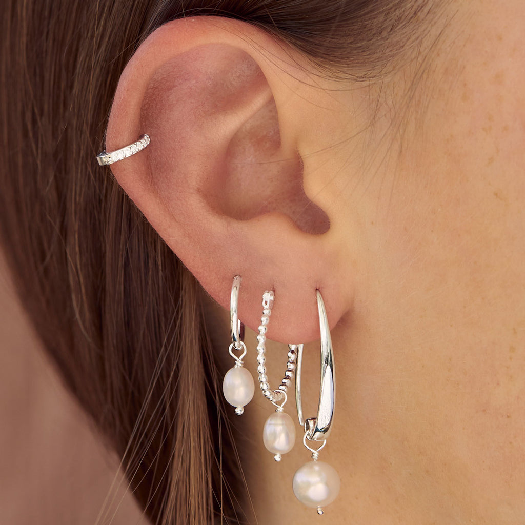 Close up shot of models ear with pearl earrings