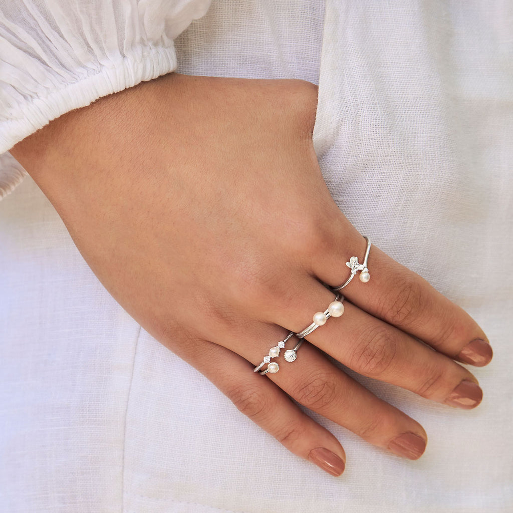 Close up of model's hand with pearl rings
