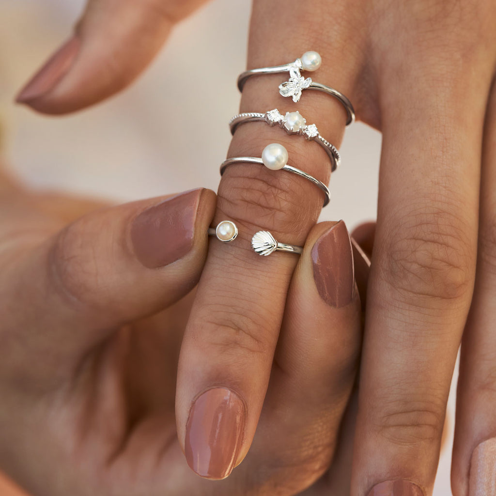 Close up shot of pearl rings on hand