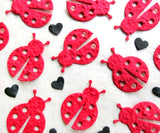 red seed paper ladybugs with black hearts