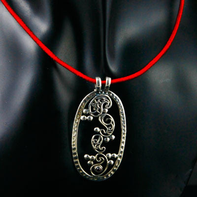 Elegant, oval pendant with four dancing paisley motifs and a garnet accent
