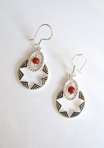 Quaint, oval dangling earrings with a garnet bead and fine black enamel work