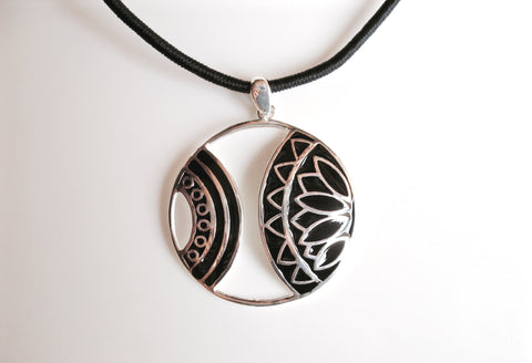 Artistic round pendant with cut outs and fine black enamel detailing