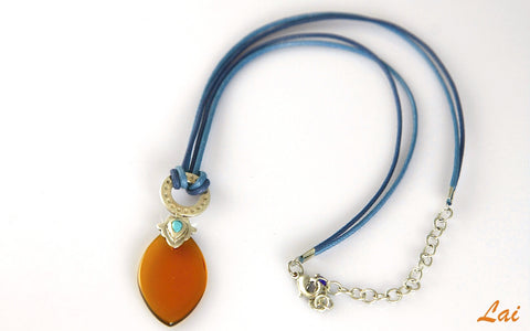 Artistic navette shape amber colour glass pendant on contrasting blue cord (PBS-4167)  Necklace, Pendant Sterling silver handcrafted jewellery. 925 pure silver jewellery. Earrings, nose pins, rings, necklaces, cufflinks, pendants, jhumkas, gold plated, bidri, gemstone jewellery. Handmade in India, fair trade, artisan jewellery.