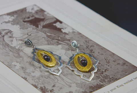 Beautiful, moroccan cut-out earrings with gold plated wire wrapping detail and a faceted garnet drop