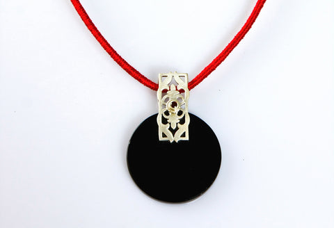 Beautiful, round black glass pendant with silver and garnet accent