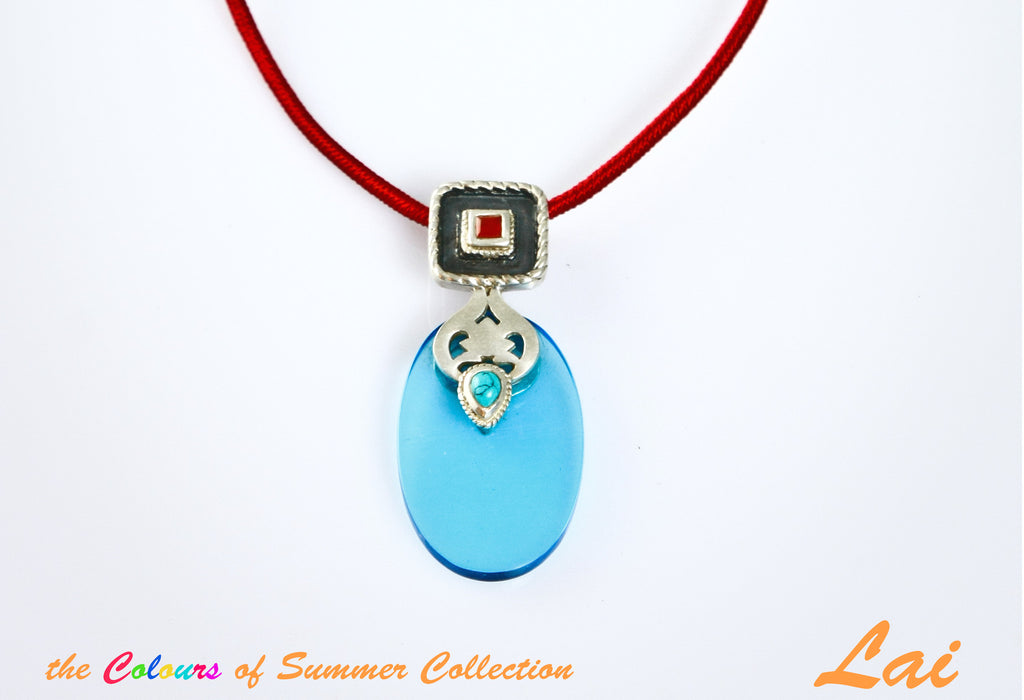 Chic, oval blue glass pendant with silver, turquoise and carnelian detailing  Necklace, Pendant Sterling silver handcrafted jewellery. 925 pure silver jewellery. Earrings, nose pins, rings, necklaces, cufflinks, pendants, jhumkas, gold plated, bidri, gemstone jewellery. Handmade in India, fair trade, artisan jewellery.