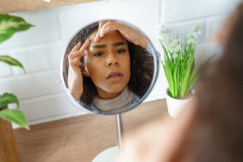 woman checking skin problems in mirror