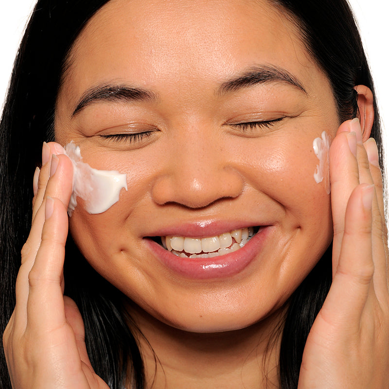 face of woman applying facial moisturizer