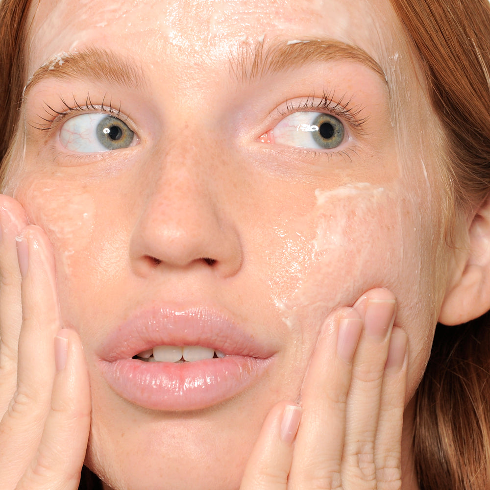 woman washing face with creamy face wash