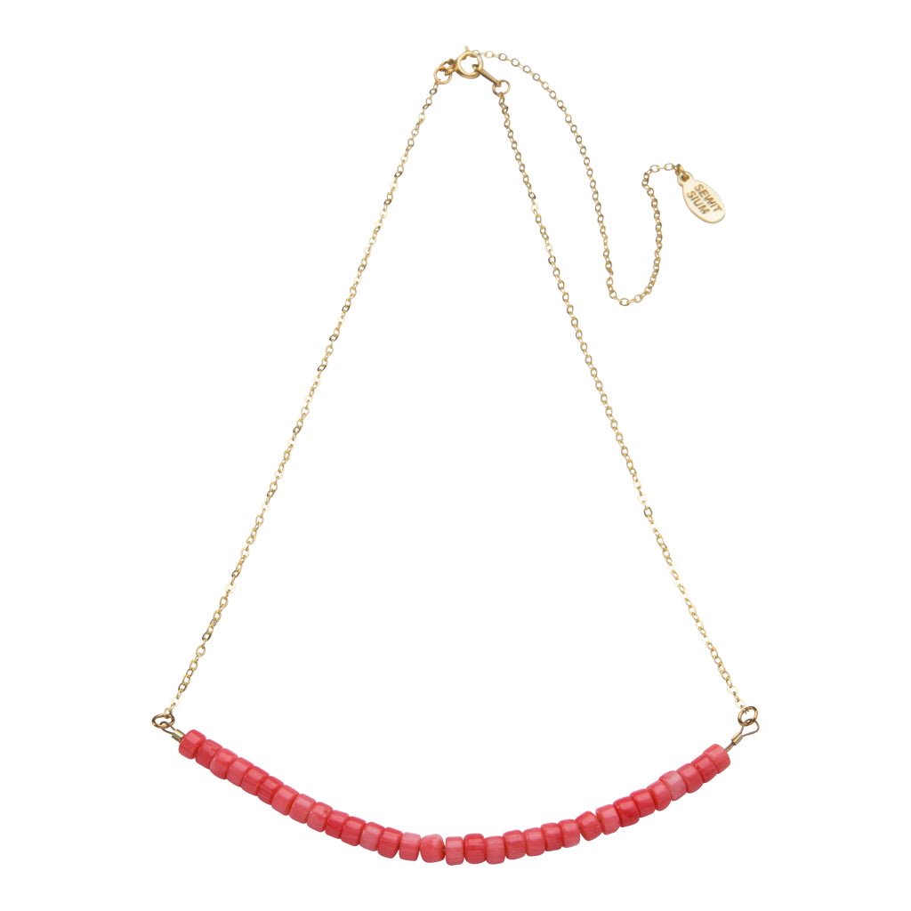 The Ma'at Necklace featuring a balanced coral bar symbolizes truth, justice and order. can be worn solo or layered, adding a vibrant pop of color