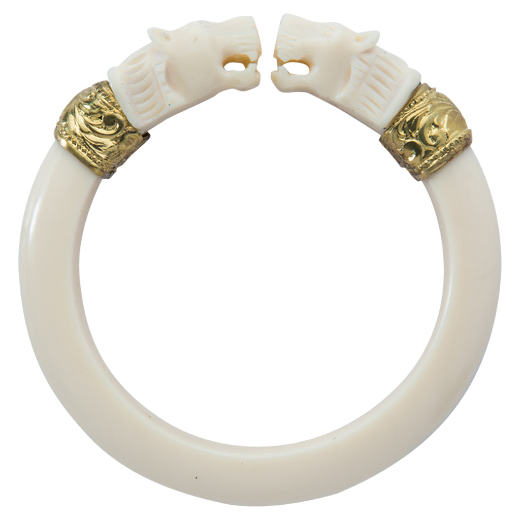 This double-headed roaring lion bangle is handmade of smooth ivory colored bakelite with repousee gold bands. Appears antique or vintage. Sewit Sium jewelry.
