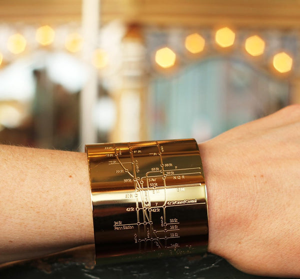 Designhype's 18k gold plated NYC Metro Cuff Subway Map bracelet with embossed lines of the MTA subway. The go-to gift for wanderlust jewelry and women who love New York City.