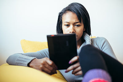 Black woman reading ebook on her tablet