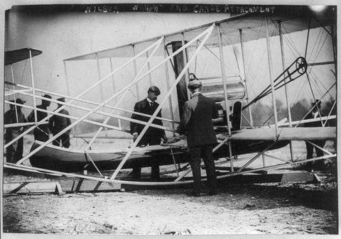 Wright brothers examining the Canoe attachment before first flight over water - Shumee